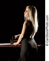 sexy blonde woman in retro style, ironing white shirt with...