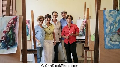 Group Of Elderly People Smiling At Camera At Art School