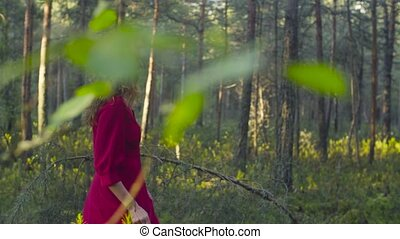 Young woman in red dress walking in the forest