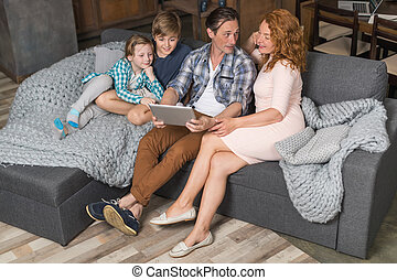 Happy Smiling Family Use Tablet Computer Sitting On Couch In...