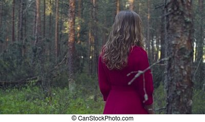 Young woman in red dress walking in the forest - Dolly shot...