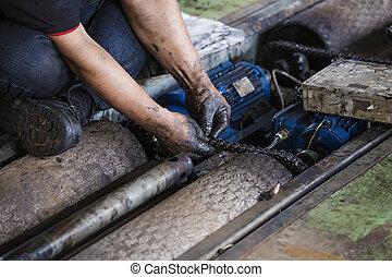 Hand during maintenance work of chain - Hand of repairman...