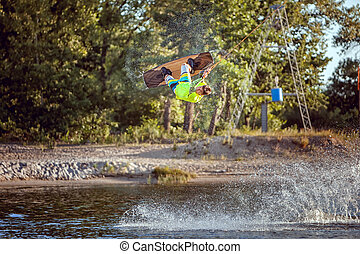 Sportsman wakeboarder during the jump. He jumped high above...