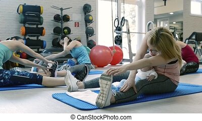 Mothers exercising with babies in gym with personal trainer....