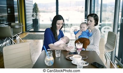 Women with babies in cafe, looking at pictures in smart...