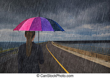 business woman holding multicolored umbrella with falling rain on road