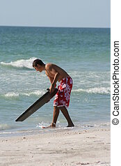 Teen on Beach with Surfboard - Teenage boy on the beach with...