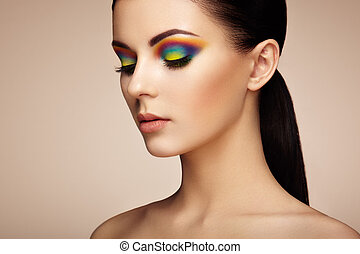 Portrait of beautiful young woman with rainbow make-up
