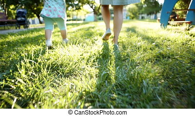 Mother and child walking on the grass - Mother and baby are...