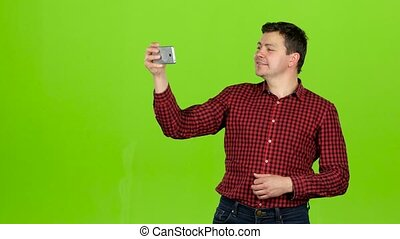 Guy takes pictures of himself, poses and smiles. Green...