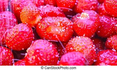 Sugar is poured onto the strawberry. Close-up.