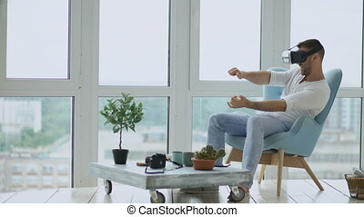 Young man have VR experience to play computer racing games using virtual reality headset sitting in chair on balcony