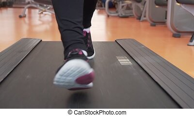 Young girl trains on a treadmill in gym stock footage video