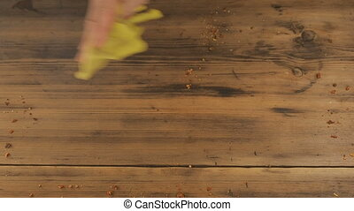 The man wipes the table of the old, brown boards, yellow...