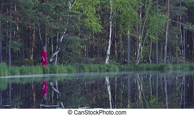 Young woman standing in the forest near the lake - Young...