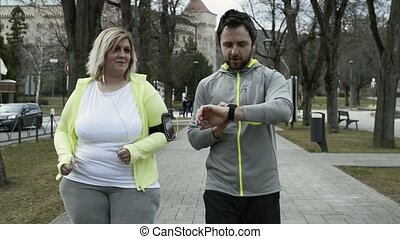 Fitness trainer in town park running with overweight woman....