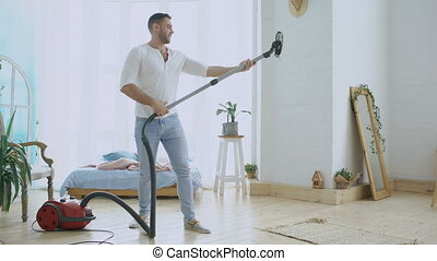 Young man having fun cleaning house with vacuum cleaner dancing like with woman