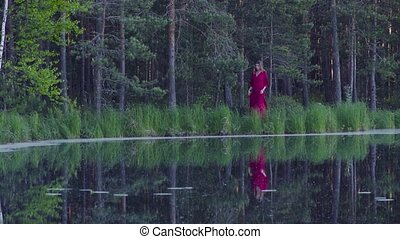Young woman walking in the forest near the lake - Young...