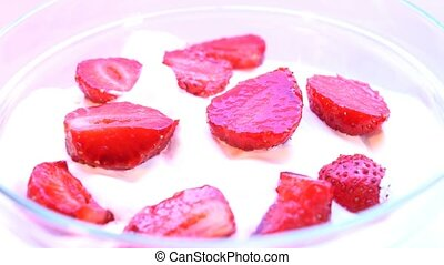 Pieces of strawberries in cream, rotating. Macro shot. looping.
