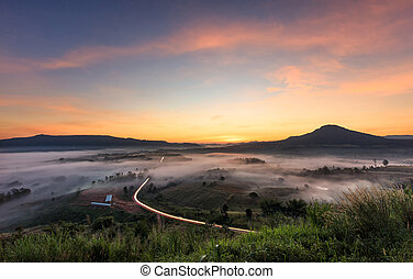 Landscape misty view. Fantastic dreamy sunrise on rocky mountains with view into misty valley below. Foggy clouds above forrest. View below to fairy landscape. Foggy forest hills.