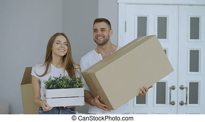 Happy couple watching their new home excited. Young woman give keys to her boyfriend and kissing him