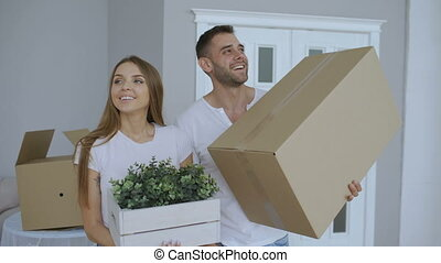 Happy couple watching their new home excited. Young man give keys to his girlfriend and kissing her