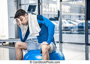 Tired young man resting on fitness ball at gym