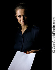 woman in dark dress isolated on black giving paper sheet -...