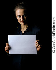 woman isolated on black background showing blank paper sheet...