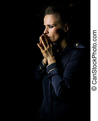 pensive woman in dark dress isolated on black background -...