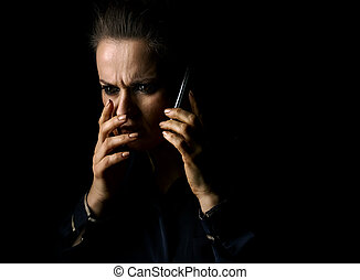 woman isolated on black background speaking on smartphone -...