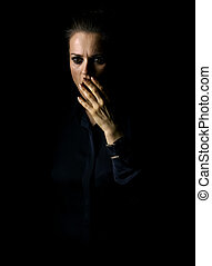 stressed woman in dark dress isolated on black background -...