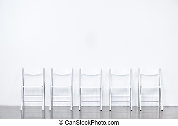 row of smart chairs at white waiting room
