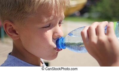guy drinks water from bottle outdoors