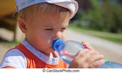baby drinks water from bottle outdoors