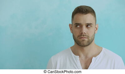 Portrait of young funny man twisting his eyes like crazy on blue background