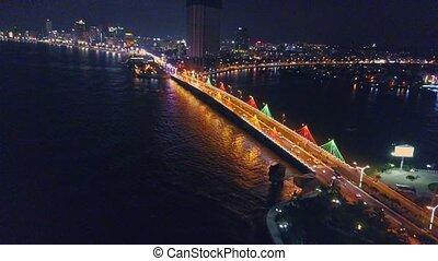 Drone Flies along Bay Bridge in Night City on Seaside -...