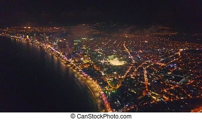 Drone Flies over Bright Night City on Seaside