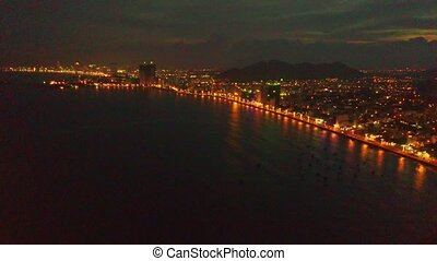 Aerial View of Dark Ocean Bay and Distant Night City -...