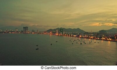 Drone Shows Evening City on Seaside against Sunset