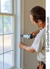 Carpenter brad using nail gun to moldings on windows,...