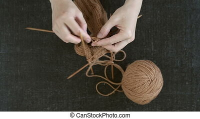 How to knit a sock. Female hands knitting a sock on a black...