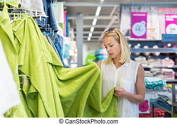 Woman choosing the right towel for her apartment in a modern...