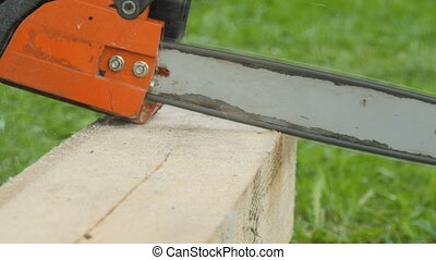 A worker cuts a wooden beam with a gasoline saw close-up