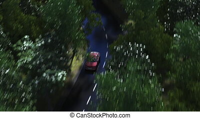 Aerial clip of red car speeding on a curvy forest road....