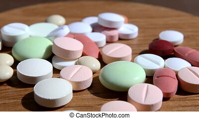 pills on rotating plate - Medicine pills of various colors...