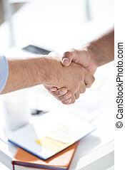 Top view of businessmen shaking hands above table with papers, business teamwork concept