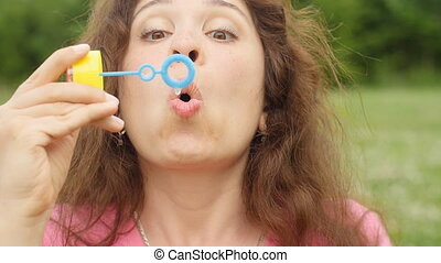Woman blowing soap bubbles at sunset in a park