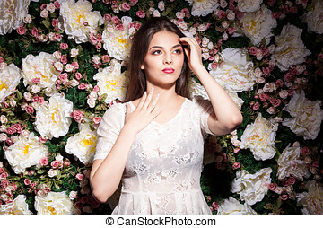 Beautiful gorgeous model on flower background in studio photo.