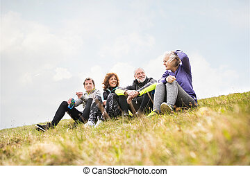 Group of senior runners outdoors, resting and talking. -...